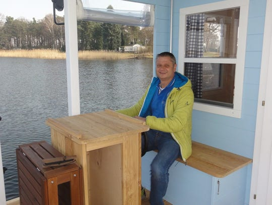Thomas Laux, 52, sits in the boathouse he leases to