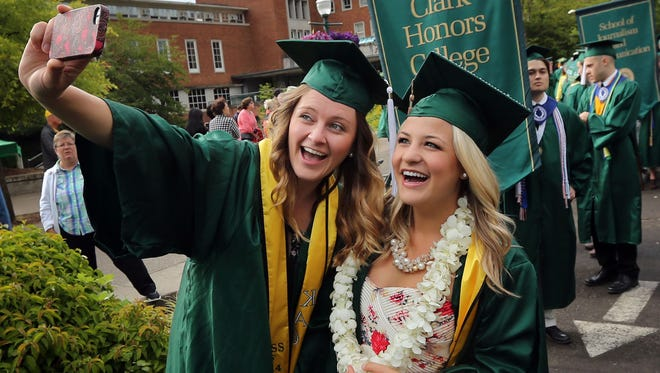 In this June 16, 2014, file photo, Brittany Rumble, left, and Jessica Whitney take a self portrait together as they wait to join the Duck Walk to the 2014 University of Oregon commencement ceremony at Matt Knight Arena in Eugene, Ore.  Oregon released graduation rates for 2013-14. The rate was 68 percent last year, meaning the state has to improve quickly if it wants to reach lofty goal of 100 percent by 2025.