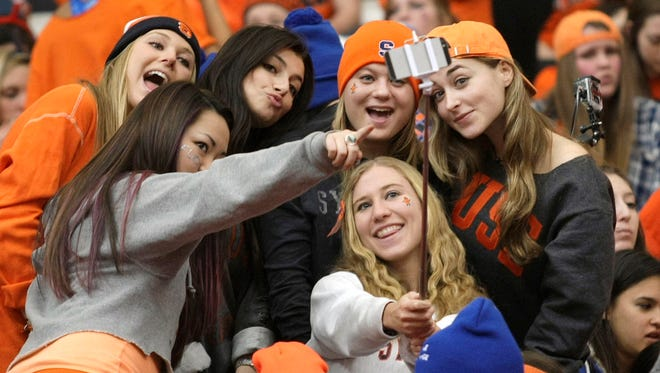 Syracuse fans shoot a selfie with a selfie stick before an NCAA college basketball game against Duke in Syracuse, N.Y.