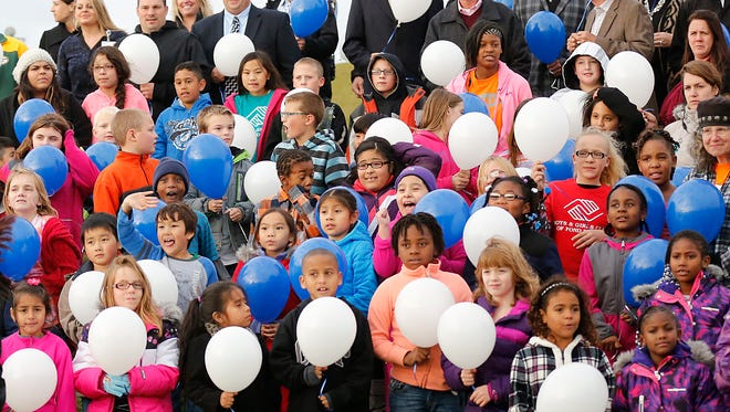 Community supporters and children from the Boys And Girls After School Clubhouse at Parkside Elementary School get ready to release balloons outside of the school Oct. 29 to celebrate the opening of the after-school location.
