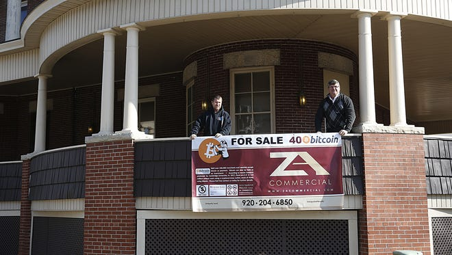Brian Pearl and Tom Ackerman hold a sign announcing the availability for the former Elks Lodge to be sold for bitcoin only.