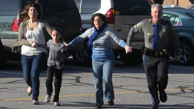 A police officer leads two women and a child from Sandy Hook Elementary School in Newtown, Conn., where a gunman opened fire, killing 26 people, including 20 children Dec. 14, 2012.