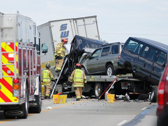 Firefighters examine the cab of the flatbed truck that
