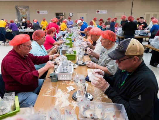Volunteers weigh and seal bags during a meal-packing