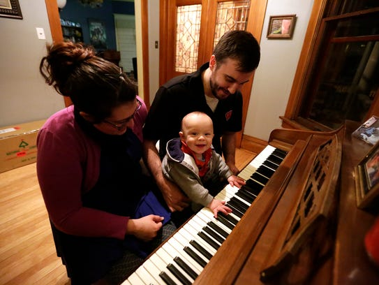Jennifer, Kylar and Seth Michels play at a piano in