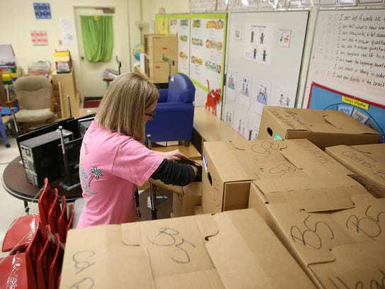 Teacher Abby Worsham puts items in a box while prepping