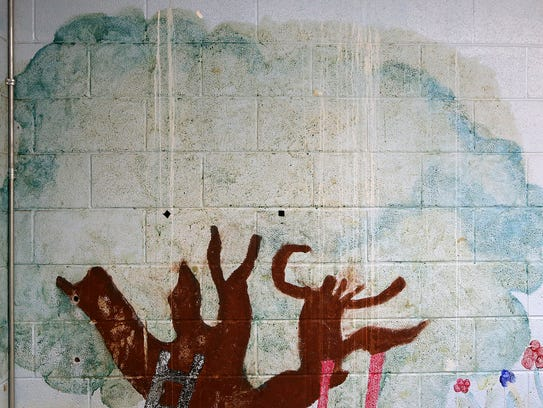 A water-damaged mural is seen inside Melanie Hatley's