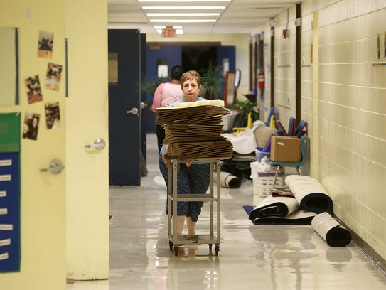 Teacher Melanie Hatley pushes a cart of boxes down