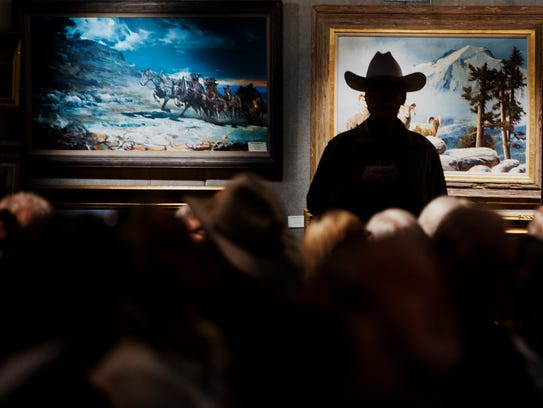A participant in a cowboy hat is silhouetted against art to be auctioned during the March in Montana Art Show at the Great Falls Elks Lodge.