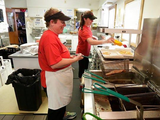 Pam Breister and Heather Schultz cook in the kitchen