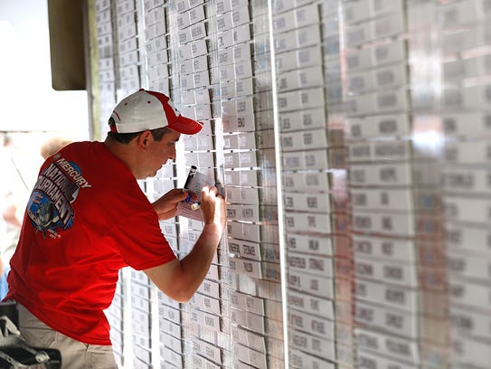 Dave Einberger updates weights on a wall of tournament