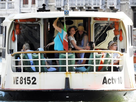 Tourists ride aboard a vaporetto, or public water bus,