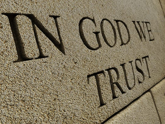 """The words """"IN GOD WE TRUST"""" carved into a stone wall."""