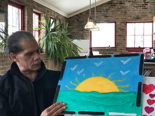 Larry Trammell holds a painting made by his son, Adam,