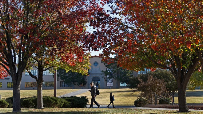 11/30/2016: NMSU students walk to class under late fall foliage on campus.