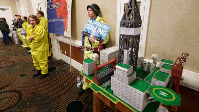 Ruchi Stair of Seattle and other demonstrators wear yellow suits intended to resemble gear worn by oil spill cleanup workers, Monday, March 5, 2018, as she stands next to a model of an offshore oil platform while attending a hearing in Olympia, Wash., organized by a coalition of environmental groups opposed to the Trump administration's proposal to expand offshore oil drilling off the Pacific Northwest coast. The hearing was held on the same day as an open house hosted by the federal Bureau of Ocean Energy Management.