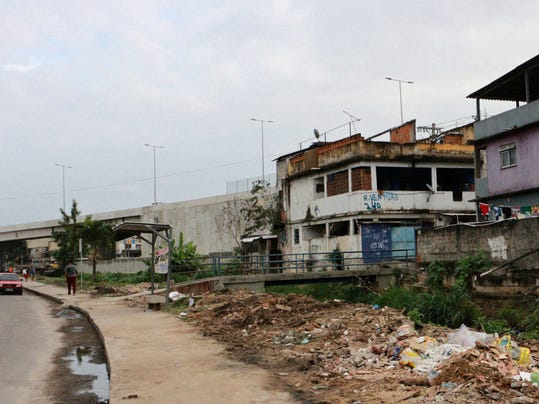 In this May 20, 2017, photo, the Bus Rapid Transit road, left back, built for last year's Rio de Janeiro's Olympics, resulted in the displacement of some residents of the Vila Uniao de Curicica area, in Rio de Janeiro, Brazil. The forced relocation experience isn't unique to Rio. London faced the same issue, as did Beijing before it. But Rio's poverty and vast inequality helped draw attention to the actions of the city and Olympic organizers. (AP Photo/Liliana Michelena)