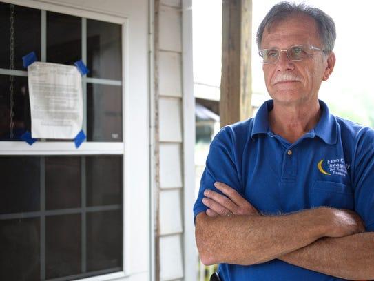 Eaton County Treasurer Bob Robinson outside a home
