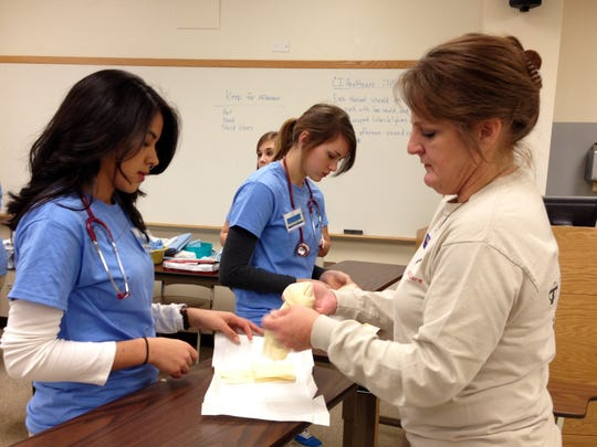 Angela Bordelon (right), a nursing professor at Louisiana State University of Alexandria, demonstrates the proper way to apply sterile gloves to Glenmora High senior Christina Rubio (far left) and Rapides High junior Cheyanne Guillory (center) at CI: Healthcare on Thursday.