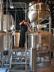Matt Bitsche stirs a batch of beer in the process