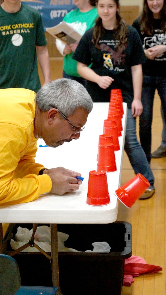 Father Stephen Fernandes of St. Joseph York competes in a game at the Catholic schools Battle of the Buildings.