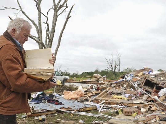 Robert Scott looks through a family Bible that he pulled out of the rubble Sunday from his Seely Drive home outside of Hamilton, Miss., after an apparent tornado touched down Saturday night.