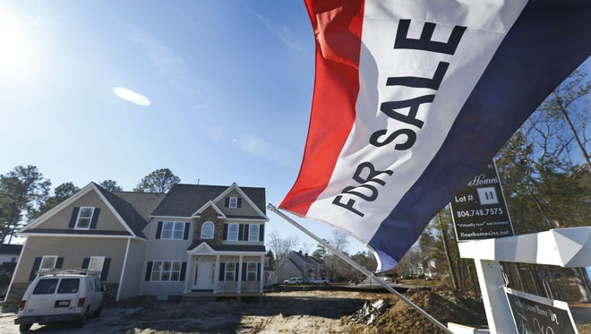 A flag advertising a newly built home for sale flaps in the breeze in Richmond, Va.