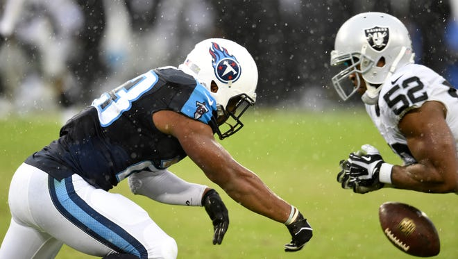 Titans running back David Cobb misses a pass while Raiders defensive end Khalil Mack defends during the fourth quarter.