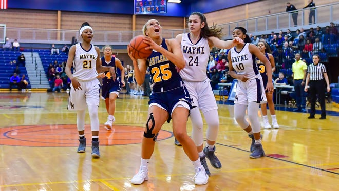 Hartland's Whitney Sollom (25), who scored a game-high 22 points, goes to the basket against Jasmine Elder (24) of Wayne Memorial in the state Class A quarterfinals on Tuesday, March 14, 2018 at Southfield A&T.