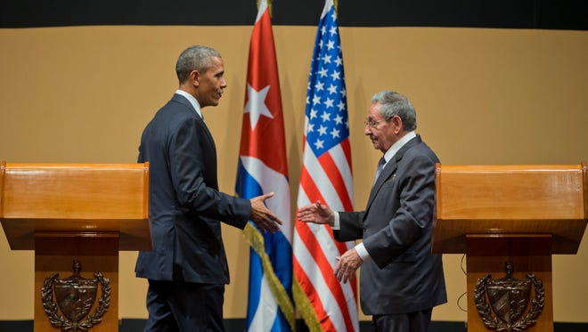 President Barack Obama with Cuban President Raul Castro prepare to shake hands at their joint news conference at the Palace of the Revolution, Monday, March 21, in Havana, Cuba.