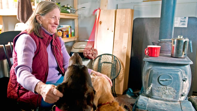 After a debilitating sickness and serious injury, Penny Owen moved back to Vermont and built a small house on 2 acres she owns in Eden. Seen with her dogs Lilly (left) and Junior  April 3.