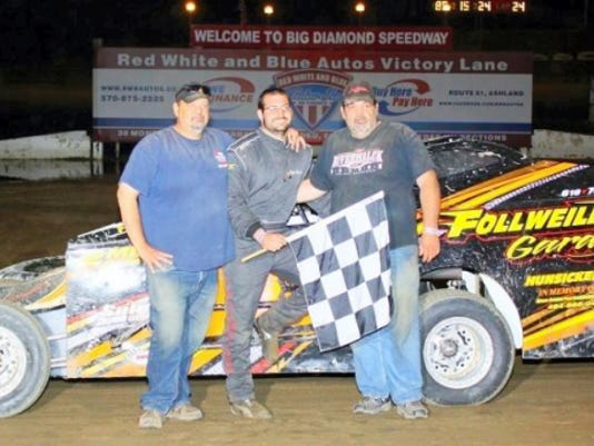 Kyle Follweiler, center, is joined in victory lane by two members of his family. It was an emotional small-block Modifieds win for Follweiler on Friday night at Big Diamond, because his grandfather passed away.