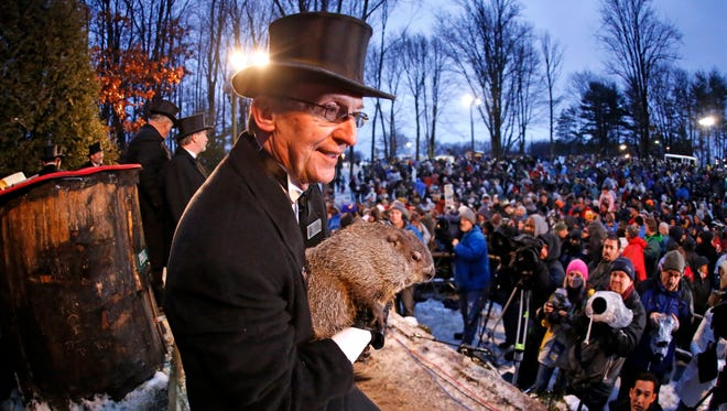 In this photo taken with a fisheye lens Groundhog Club handler Ron Ploucha holds Punxsutawney Phil, the weather prognosticating groundhog, during the 129th celebration of Groundhog Day on Gobbler's Knob in Punxsutawney, Pa., Feb. 2, 2015. Phil saw his shadow, predicting six more weeks of winter weather.
