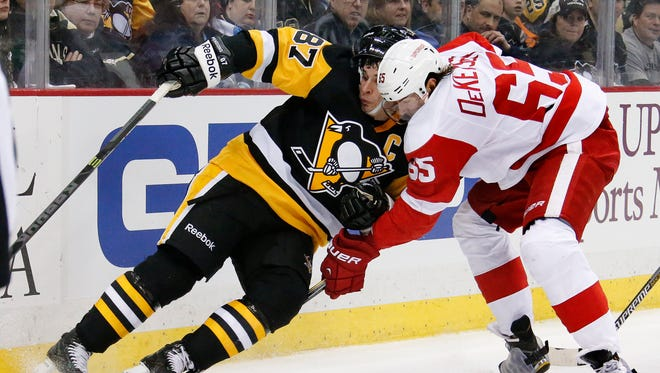Detroit Red Wings defenseman Danny DeKeyser (65) checks the Pittsburgh Penguins' Sidney Crosby off the puck in Pittsburgh on March 15, 2015.