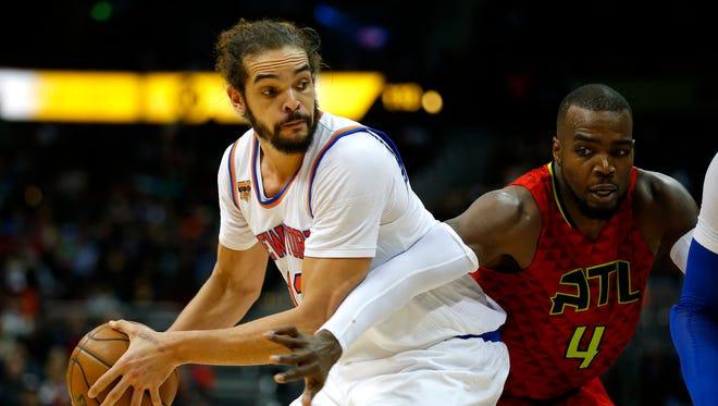 New York Knicks center Joakim Noah (13) looks to pass as Atlanta Hawks forward Paul Millsap (4) is defending during Sunday's game.