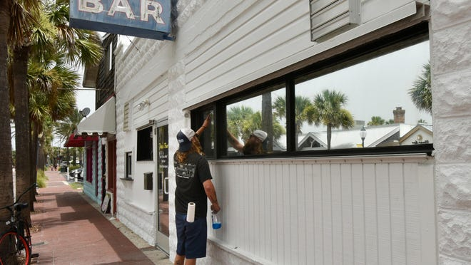 An employee at Pete's Bar in Neptune Beach cleans windows on Fridaiy after the bar closed. The Florida Department of Business and Professional Regulation had just ordered a halt to on-premises alcohol consumption across the state effective immediately.