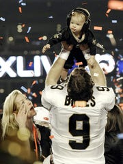 Super Bowl MVP Drew Brees raises his son Baylen in celebration of defeating the Colts, 31-17, in Miami in 2010.