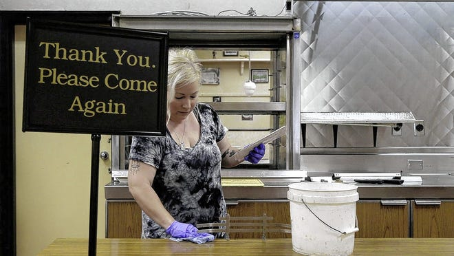 Richelle Buchanan scrubs the counter June 2 during cleanup efforts at Nancy's Home Cooking. The restaurant's new location on Lynn Street in downtown Columbus was broken into and vandalized during recent protests.