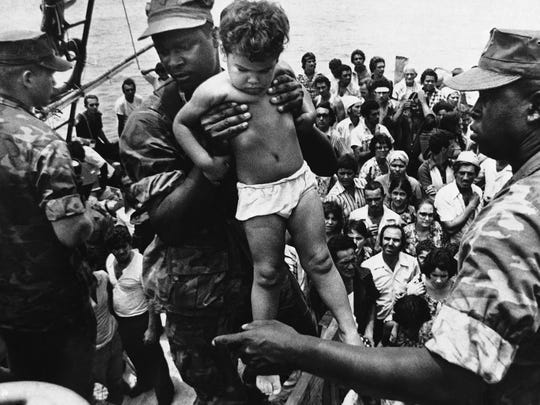 A U.S. Marine helps a young Cuban child off one of the refugee boats in Key West on May 10, 1980. Marines were called in to relieve the local authorities, who were overworked by the massive exodus of Cubans from Mariel, who were coming to Florida in any boat they could find.