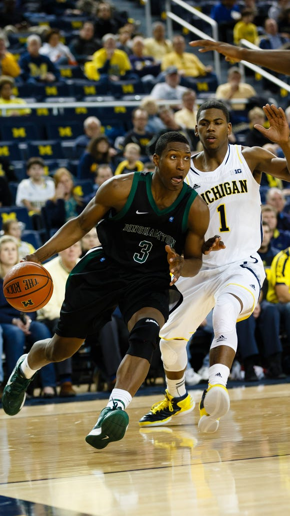 Binghamton player Jordan Reed dribbles along the baseline with a Michigan defender trailing behind him.