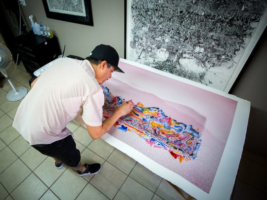 Artist Noah MacDonald, here working on a watercolor at his studio Camino Tattoo and Fine Art Studio, 501 E Hadley Ave., says he enjoys working in a variety of media and styles.