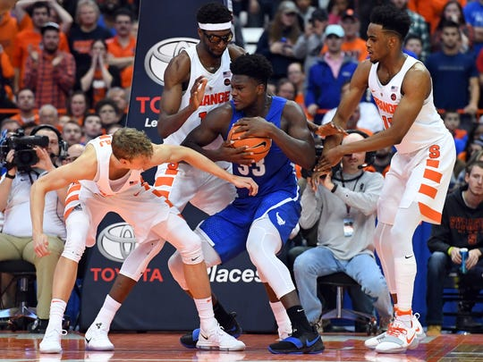 Buffalo forward Nick Perkins (33) controls the ball while Syracuse forward Marek Dolezaj (21), center Paschal Chukwu (13) and forward Oshae Brissett (11) defend during the second half Tuesday at the Carrier Dome.