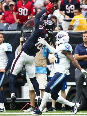 Houston Texans wide receiver DeAndre Hopkins makes a reception as Tennessee Titans cornerback Brice McCain defends during the second quarter at NRG Stadium. Mandatory Credit: