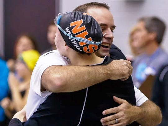 Northville coach Brian McNeff congratulates senior Laura Westphal, who figured in four first-place finishes.