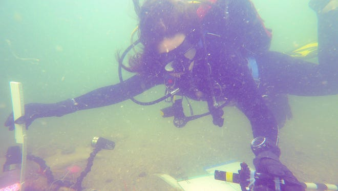 Nicole Grinnan measures a section of a 7,000-year-old archaeological site found in the Gulf of Mexico.