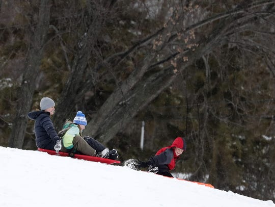 Sarah Bleier, of Neenah, sleds down a hill with her