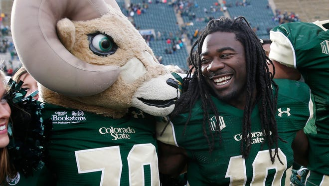 Colorado State mascot Cam the Ram, left, celebrates with running back Dee Hart after Hart scored six touchdowns against New Mexico on Nov. 22, 2014.