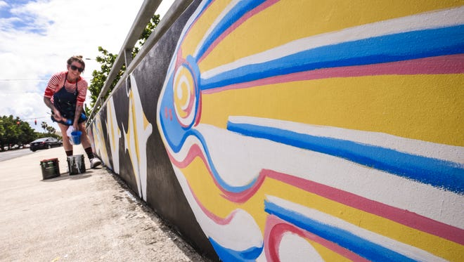 Artist Lindsay Kane adds some detail lines to paintings of marine fish on the Hagåtña Bridge on Thursday, May 4, 2017. The mural project was commissioned by the Islandwide Beautification Task Force to coincide with the 29th Guam Micronesia Island Fair, Lindsay said. More artists are creating murals at several locations in connection with a traveling art festival on Guam.