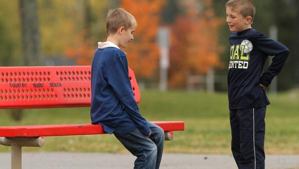 Logan Bissett, left, and his friend Ethan Sandola at the Buddy Bench, one of two such benches in use at Country Elementary School.