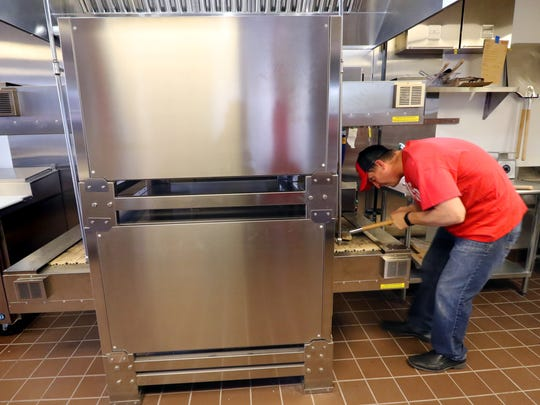 Gary Plassmeyer cleans the continuous feed deck of a two-tier oven that can bake a pizza in under three minutes at 9th Slice Pizza Co. that opened Nov. 6 at 5620 S. 108th St. in the former Kmart shopping center in Hales Corners.